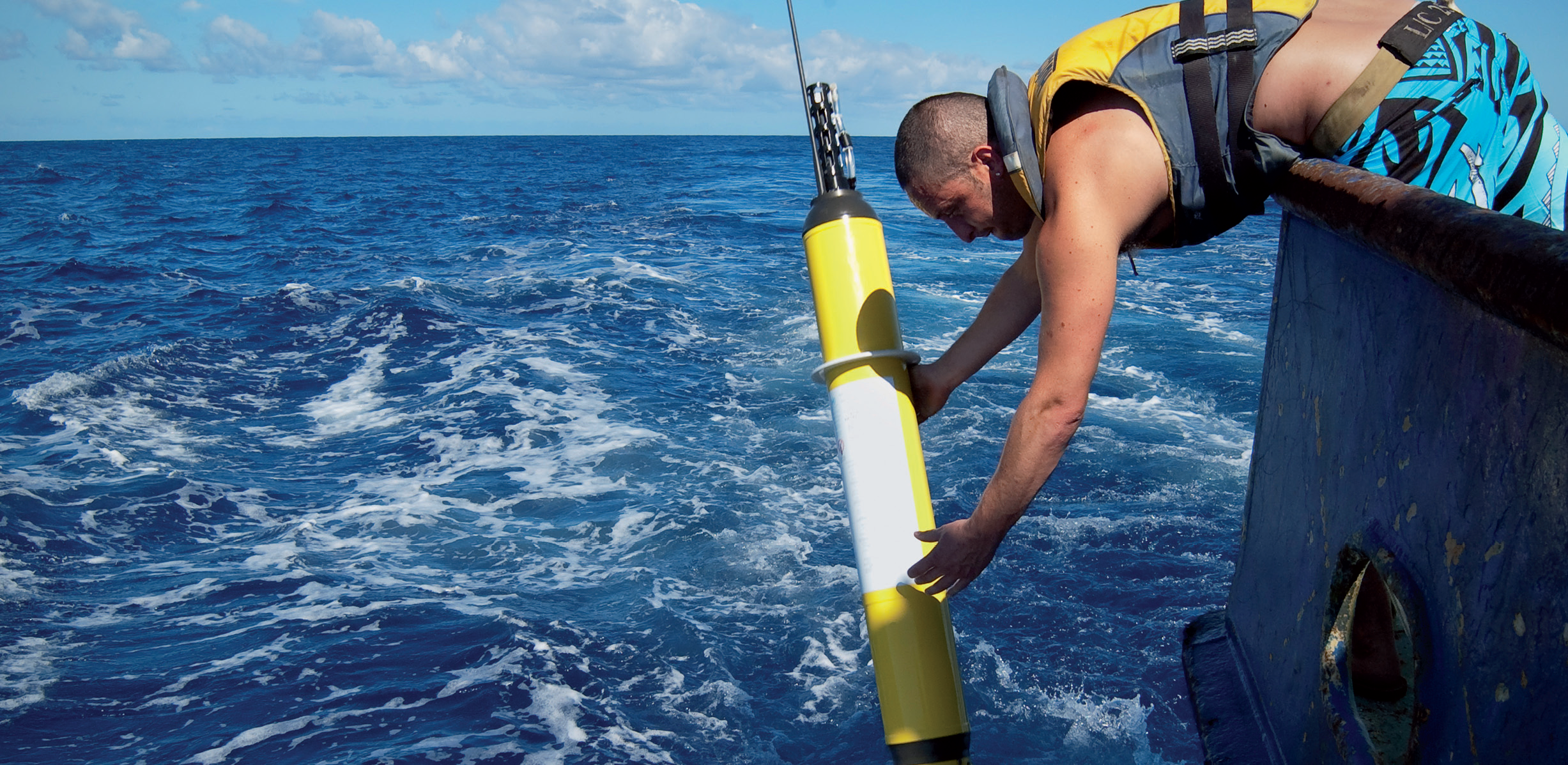 A person wearing a life jacket leans over the edge of a boat, releasing a yellow, cylindrical Argo float device from both hands into the ocean.